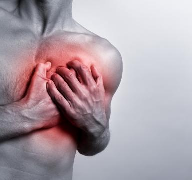 A young man clutches his chest in panic at the onset of a painful heart attack. His chest glows red indicating the source of the pain